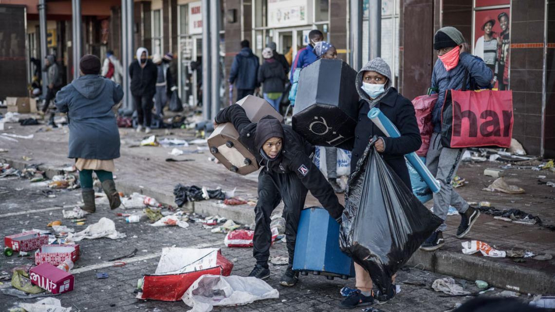 Looters take away items from a vandalised mall in Vosloorus, on July 14, 2021. The raging unrest first erupted last Friday after former president Jacob Zuma started serving a 15-month term for contempt, having snubbed a probe into the corruption that stained his nine years in power.