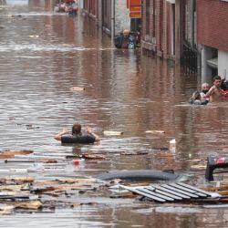 Una mujer intenta moverse en una calle inundada tras las fuertes lluvias en Lieja. | Foto:Bruno Fahy / Belga / AFP
