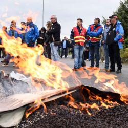 Empleados de EDF (Electricite De France) de pie frente a la quema de pallets durante una concentración en la entrada de la central eléctrica de carbón de EDF de Cordemais, al oeste de Francia, para protestar contra el abandono del proyecto Ecocombust que consiste en sustituir el carbón por pellets de biomasa densificada. | Foto:Sebastien Salom-Gomis / AFP
