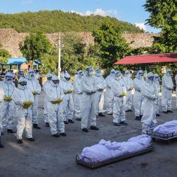 Voluntarios con equipo de protección personal rezan frente a los cuerpos de las personas que murieron por el coronavirus Covid-19 durante su funeral en un cementerio en Mandalay. | Foto:STR / AFP