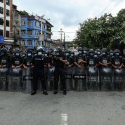 La policía monta guardia mientras los partidarios del primer ministro provisional de Nepal, KP Sharma Oli, y los miembros del Partido Comunista de Nepal-Unión Marxista-Leninista (CPN-UML) corean consignas contra la decisión del Tribunal Supremo de destituir al primer ministro en funciones y restaurar el parlamento disuelto, en Katmandú. | Foto:Prakash Mathema / AFP