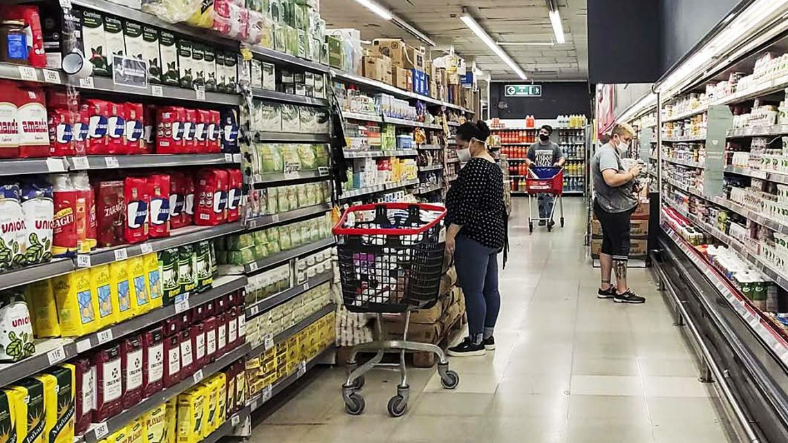 A shopper checks prices in a supermarket in Buenos Aires.