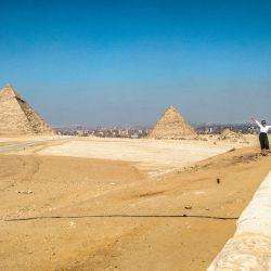 Un turista posa para la cámara en un promontorio con vistas a la Gran Pirámide de Keops, la Pirámide de Kefrén y la Pirámide de Menkheres en la antigua necrópolis de Giza en las afueras del oeste de la ciudad gemela de la capital egipcia. | Foto:Khaled Desouki / AFP