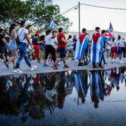 Personas sostienen banderas cubanas y estadounidenses mientras marchan durante una protesta que muestra el apoyo a los cubanos que se manifiestan contra su gobierno, en Hialeah, Florida. | Foto:Eva Marie Uzcategui / AFP