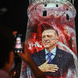 Un hombre toma una foto de la torre de Gálata, donde se exhibe un retrato del presidente turco Recep Tayyip Erdogan, con motivo del Día de la Democracia y la Unidad Nacional en Estambul.   Foto:Ozan Kose / AFP