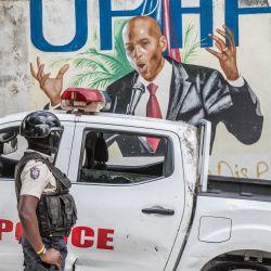 Un agente de policía permanece junto a una pared pintada con un mural del difunto presidente haitiano Jovenel Moise después de que agentes del FBI y equipos forenses realizaran registros en su residencia en Puerto Príncipe, tras su asesinato. | Foto:Valerie Baeriswyl / AFP