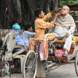 Un hombre se afeita la barba mientras se sienta en un rickshaw en una acera de Amritsar. | Foto:Narinder Nanu / AFP