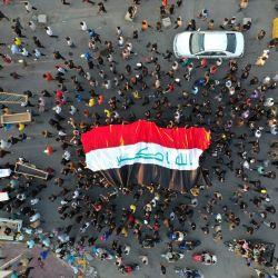 Esta vista aérea muestra a personas desplegando una gran bandera nacional y colocando ataúdes falsos frente a la sala de aislamiento de coronavirus del hospital Al-Hussein, devastada por el incendio, durante una protesta en la ciudad de Nasiriyah, en el sur de Irak. | Foto:Asaad Niazi / AFP