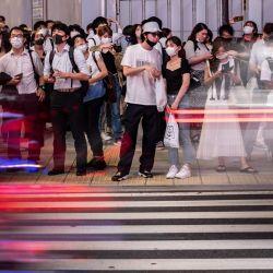 Los peatones esperan para cruzar una carretera en el distrito de Shinjuku, en Tokio. | Foto:Philip Fong / AFP
