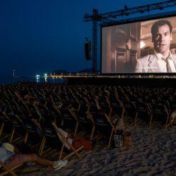 La gente ve una película en el cine al aire libre de Macé Beach en la Croisette de Canne al margen de la 74ª edición del Festival de Cine de Cannes en el sur de Francia. | Foto: John Macdougall / AFP
