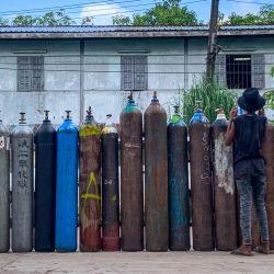 Esta foto muestra a personas que esperan para llenar botes de oxígeno vacíos fuera de una fábrica en Yangon, en medio de un aumento en el número de casos de coronavirus Covid-19. | Foto:Ye Aung Thu / AFP