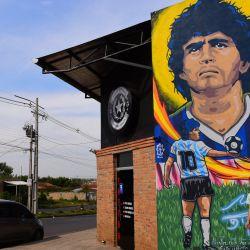El artista del tatuaje paraguayo y nuevo jugador de River Plate de Paraguay, Carlos Rodríguez, posa con su mural del fallecido futbolista Diego Maradona, en Paraguay. | Foto:Norberto Duarte / AFP