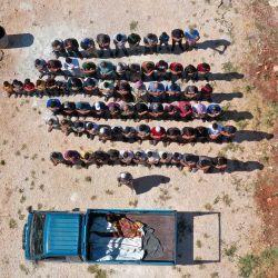 Una vista aérea muestra a los dolientes rezando sobre los cuerpos de tres niños, que murieron en un bombardeo de artillería del régimen en las afueras de la ciudad de Fuaa, durante una procesión fúnebre en un cementerio en Binnish en la provincia noroccidental de Idlib, controlada por los rebeldes. | Foto:Omar Haj Kadour / AFP