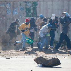 Personas huyen de los Servicios de Policía de Sudáfrica tras los saqueos y vandalismo esporádicos en el centro comercial Lotsoho, en el municipio de Katlehong, al este de Johannesburgo.   Foto:Phill Magakoe / AFP