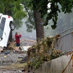 Un hombre junto a un coche destruido toma una foto de la zona devastada tras las inundaciones que causaron grandes daños en Bad Neuenahr-Ahrweiler, al oeste de Alemania. | Foto:Christof Stache / AFP