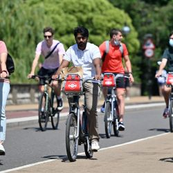 Cyclists pedal on short-term hire bicycles in the sunshine in Hyde Park, central London in July 2021.