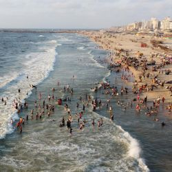 Esta vista aérea muestra a palestinos nadando en el Mediterráneo en medio de las altas temperaturas del verano, en la orilla de la ciudad de Gaza.   Foto:Mohammed Abed / AFP