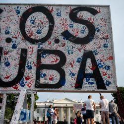 Unas personas pasan con un cartel colocado durante una protesta que muestra el apoyo a los cubanos que se manifiestan contra su gobierno frente a la Casa Blanca en Washington, DC.   Foto:Andrew Caballero-Reynolds / AFP