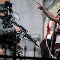 Un hombre palestino discute con los guardias fronterizos israelíes que bloquean una calle para una procesión de judíos religiosos en Tisha B'Av que marchan hacia el santuario de Atnaeil Ben Kinaz en la ciudad conflictiva de Hebrón, en la Cisjordania ocupada por Israel.   Foto:Mosab Shawer / AFP