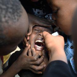 Un trabajador sanitario de la comunidad administra una vacuna contra la poliomielitis, un virus altamente contagioso que puede causar parálisis y discapacidad de por vida, o incluso la muerte, durante la campaña de inmunización contra la poliomielitis en Kiamako, Nairobi.   Foto:Simon Maina / AFP
