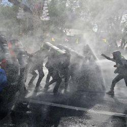 Manifestantes prodemocráticos se enfrentan a la policía antidisturbios mientras marchan hacia la Casa de Gobierno para pedir la dimisión del primer ministro de Tailandia, Prayut Chan-O-Cha, en Bangkok.   Foto:Lillian Suwanrumpha / AFP