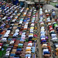 Musulmanes rezan en la calle frente a la mezquita de Adjame, un barrio popular de Abiyán, durante las celebraciones del Eid al-Adha. | Foto:Sia Kambou / AFP