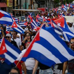 Personas ondean banderas cubanas mientras marchan durante una protesta en apoyo a los cubanos que se manifiestan contra su gobierno, en Union City, Nueva Jersey. | Foto:Kena Betancur / AFP