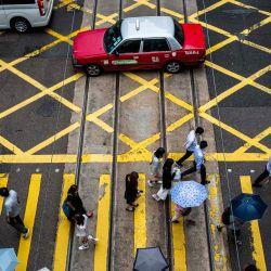 Los peatones cruzan una calle en Hong Kong. | Foto:Isaac Lawrence / AFP