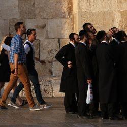 La gente pasa junto a un grupo de hombres judíos ultraortodoxos reunidos frente a la entrada de la Puerta de Jaffa de la Ciudad Vieja de Jerusalén.   Foto:Emmanuel Dunand / AFP