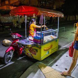 Los clientes esperan a que un vendedor prepare sus pedidos de comida para llevar en Bangkok, antes de la restricción del toque de queda nocturno implementado para reducir la propagación del coronavirus Covid-19.   Foto:Candida NG / AFP