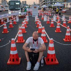 Un hombre mira su teléfono móvil en el centro de autobuses del centro de medios olímpicos en Tokio, antes de los Juegos Olímpicos de Tokio 2020.   Foto:Loic Venance / AFP