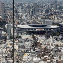 Una mujer toma fotos del Estadio Olímpico desde la plataforma de observación Shibuya Sky en Tokio antes de los Juegos Olímpicos de Tokio 2020.   Foto:Behrouz Mehri / AFP