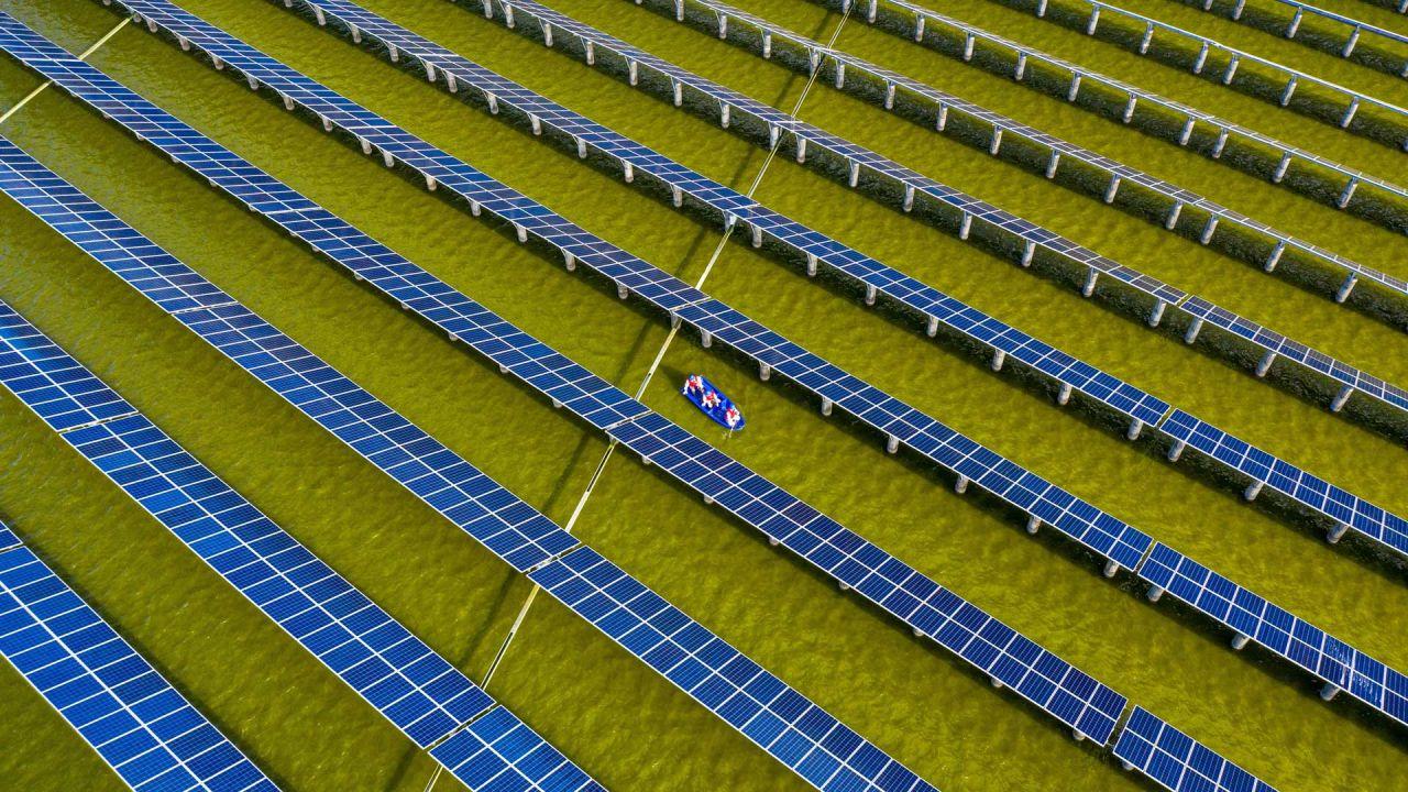 Esta foto aérea muestra a trabajadores eléctricos en un barco mientras revisan los paneles solares de una estación de energía fotovoltaica construida en un estanque de peces en Haian, en la provincia oriental china de Jiangsu.   Foto:STR / AFP