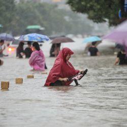 Esta foto muestra a personas vadeando las aguas de las inundaciones a lo largo de una calle tras las fuertes lluvias en Zhengzhou, en la provincia central china de Henan.   Foto:STR / AFP