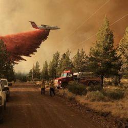 Esta foto proporcionada por el Departamento Forestal de Oregón muestra un avión cisterna de extinción de incendios lanzando un retardante sobre el incendio de Grandview, cerca de Sisters, Oregón.   Foto:Handout / Departamento Forestal de Oregón / AFP