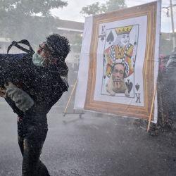 Un manifestante prodemocrático lanza un objeto mientras otros se ponen a cubierto del cañón de agua de la policía tras una imagen despectiva del primer ministro de Tailandia, Prayut-Chan-O-Cha, mientras marchan hacia la Casa de Gobierno para pedir su dimisión en Bangkok.   Foto:Lillian Suwanrumpha / AFP