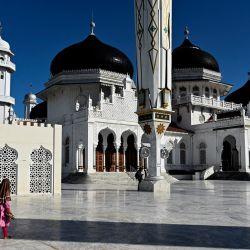 Una mujer y su hijo caminan junto a la Gran Mezquita de Baiturrahman durante el festival Eid al-Adha en Banda Aceh Aceh.   Foto:Chideer Mahyuddin / AFP