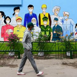 Un hombre pasa junto a un mural que representa a los trabajadores de primera línea del coronavirus Covid-19 en el exterior de un edificio en Hanoi.   Foto:Nhac Nguyen / AFP