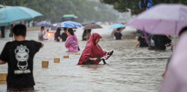Esta foto muestra a personas vadeando las aguas de las inundaciones a lo largo de una calle tras las fuertes lluvias en Zhengzhou, en la provincia central china de Henan.