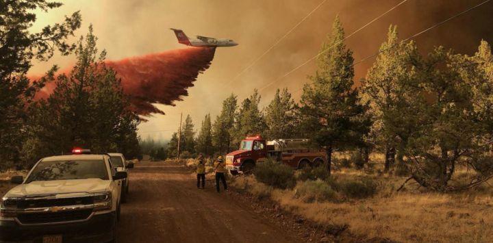 Esta foto proporcionada por el Departamento Forestal de Oregón muestra un avión cisterna de extinción de incendios lanzando un retardante sobre el incendio de Grandview, cerca de Sisters, Oregón.