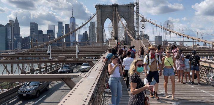 La gente se ve cruzando la pasarela peatonal del puente de Brooklyn en Nueva York.
