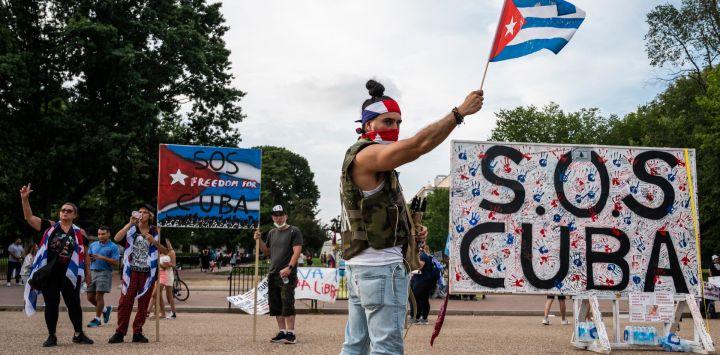 Manifestantes gesticulan y sostienen banderas durante una protesta que muestra el apoyo a los cubanos que se manifiestan contra su gobierno frente a la Casa Blanca en Washington, DC.