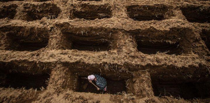 Un trabajador de un cementerio cava los agujeros de las tumbas de las víctimas del coronavirus Covid-19 en el cementerio de Setu Gede en Bogor, Java Occidental.