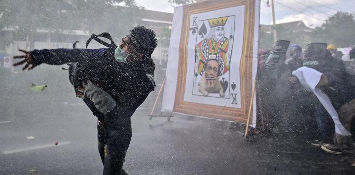 Un manifestante prodemocrático lanza un objeto mientras otros se ponen a cubierto del cañón de agua de la policía tras una imagen despectiva del primer ministro de Tailandia, Prayut-Chan-O-Cha, mientras marchan hacia la Casa de Gobierno para pedir su dimisión en Bangkok.