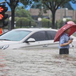Esta foto muestra a un hombre vadeando un coche sumergido a lo largo de una calle inundada tras las fuertes lluvias en Zhengzhou, en la provincia central china de Henan.   Foto:STR / AFP