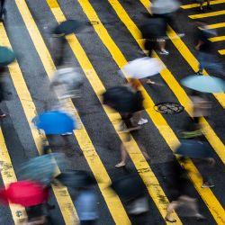 Peatones con paraguas cruzan una carretera en Hong Kong, mientras los patrones climáticos del tifón Cempaka traen fuertes lluvias a la ciudad.   Foto:Isaac Lawrence / AFP