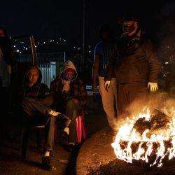 Miembros del Foro de Policía Comunitaria de Phoenix, un grupo de movilización de base en el que participan residentes locales, sentados alrededor de un neumático incendiado durante una vigilancia en Durban.   Foto:Marco Longari / AFP
