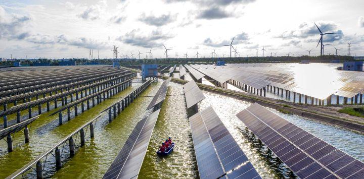 Esta foto muestra a trabajadores eléctricos en un barco mientras revisan los paneles solares en una estación de energía fotovoltaica construida en un estanque de peces en Haian, en la provincia oriental china de Jiangsu.