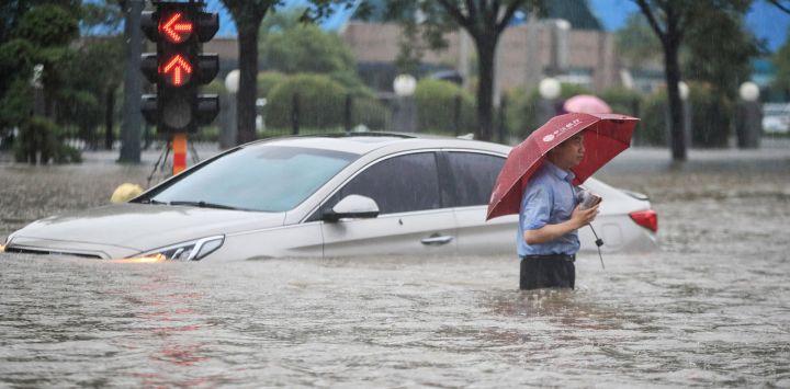 Esta foto muestra a un hombre vadeando un coche sumergido a lo largo de una calle inundada tras las fuertes lluvias en Zhengzhou, en la provincia central china de Henan.