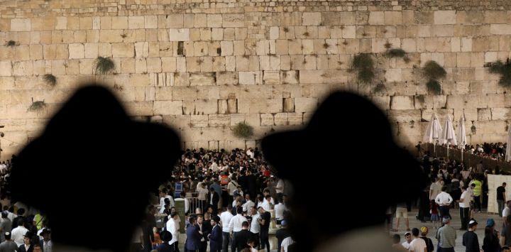 Hombres judíos ortodoxos rezan y leen el libro de Eicha (Libro de las Lamentaciones) en el Muro Occidental de la Ciudad Vieja de Jerusalén.